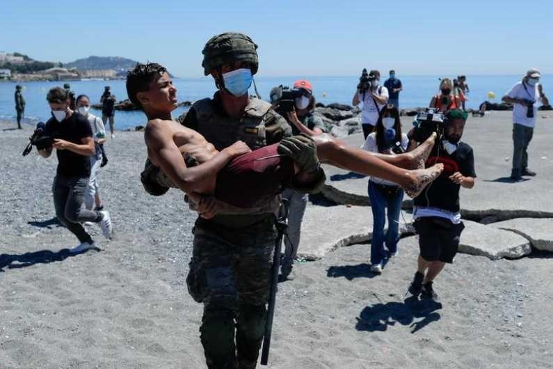 मोरोक्कोहून पोहून येताना तब्येत बिघडलेल्या लहान मुलांना स्पेनच्या सैनिकांकडून उपचारही केले जात आहेत. (Photo Credit : Reuters)