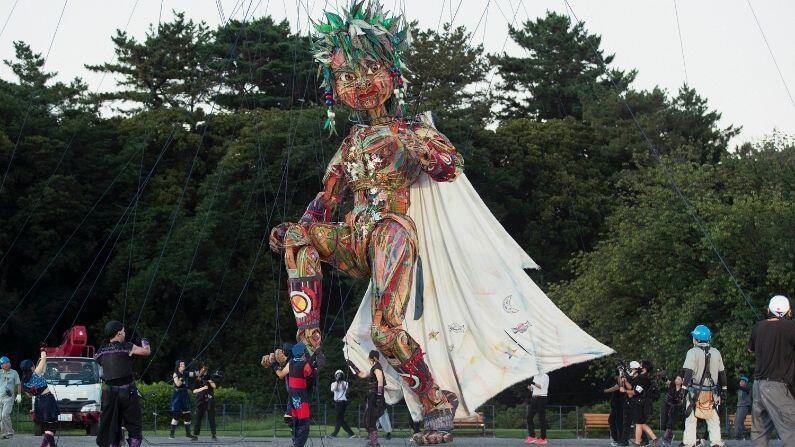 टोकियोच्या एका पार्कमधील सांस्कृतिक महोत्सवात 10 मीटर उंचीची बाहुली सादर केली जाईल. 'मोक्को' नावाची ही रंगीबेरंगी बाहुली मोठ्या क्रेनच्या मदतीने पार्कमध्ये आणण्यात आलीय.