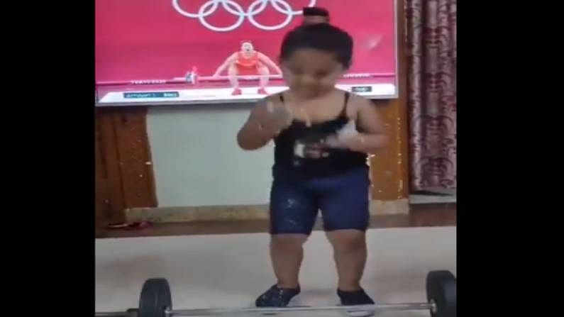 Little girl trying to weight lifting
